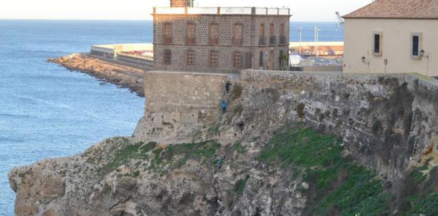 Varios chicos bajan por un muro junto al faro del puerto de Melilla | N.C.