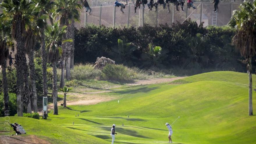Al menos doce inmigrantes, encaramados en la valla de Melilla frente al campo de golf situado al lado de la alambrada que separa la ciudad autónoma de Marruecos/ Fotografía: José Palazón-Prodein
