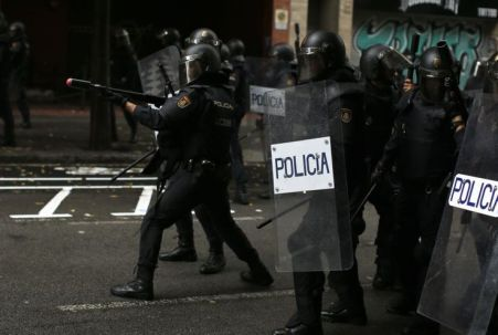 Descripción : A Spanish National Police officer aims ar rubber-bullet rifle at pro-referendum supporters in Barcelona Sunday, Oct. 1 2017. Catalonia's planned referendum on secession is due to be held Sunday by the pro-independence Catalan government but Spain's government calls the vote illegal, since it violates the constitution, and the country's Constitutional Court has ordered it suspended.