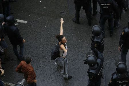 Descripción : A woman holds her hands up next Spanish National Police as they try to block voters from reaching a voting site at a school assigned to be a polling station by the Catalan government in Barcelona, Spain, Sunday, 1 Oct. 2017. Catalan pro-referendum supporters vowed Saturday to ignore a police ultimatum to leave the schools they are occupying to use in a vote seeking independence from Spain.