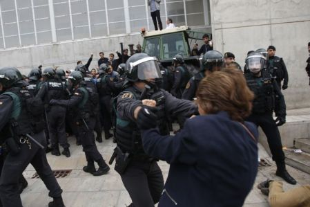 Civil guards clear people away from the entrance of a sports center, assigned to be a polling station by the Catalan government in Sant Julia de Ramis, near Girona, Spain, Sunday, Oct. 1, 2017. Scuffles have erupted as voters protested as dozens of anti-rioting police broke into a polling station where the regional leader was expected to show up for voting on Sunday.