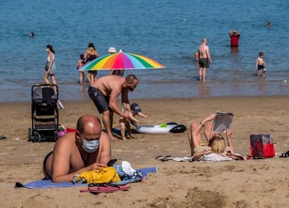 Los bañistas usan mascarillas en la playa de Las Canteras en Tenerife.