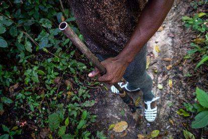 Ahmed Fofana caza carne de animales silvestres.  Su arma perteneció a su abuelo y está reforzada con cinta adhesiva.