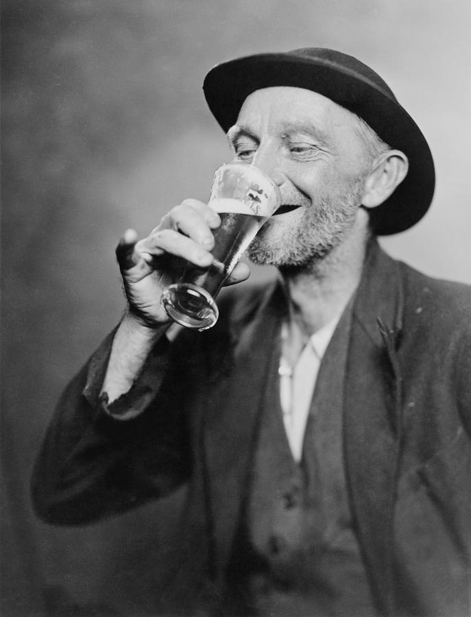 Happy old man drinking glass of beer, 1937.