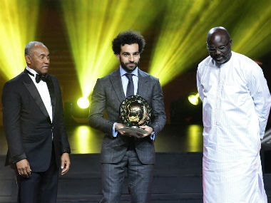 CAF president Ahmad Ahmad (L) poses after he handing the 2018 African Footballer of the Year Award to Liverpool's Egyptian forward Mohamed Salah (C) past Liberian President George Weah during an award ceremony. AFP