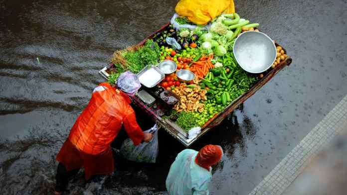 A vegetable vendor pushes his cart through a flooded street.