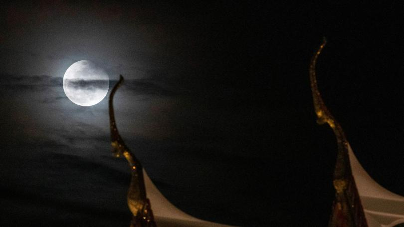 A moon is observed behind the Suthat temple in Bangkok, Thailand, (AP Photo/Sakchai Lalit)