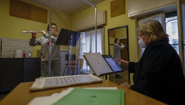 Linda Facchinetti plays her flute behind a transparent panel to curb the spread of COVID-19. Image via The Associated Press/Antonio Calanni