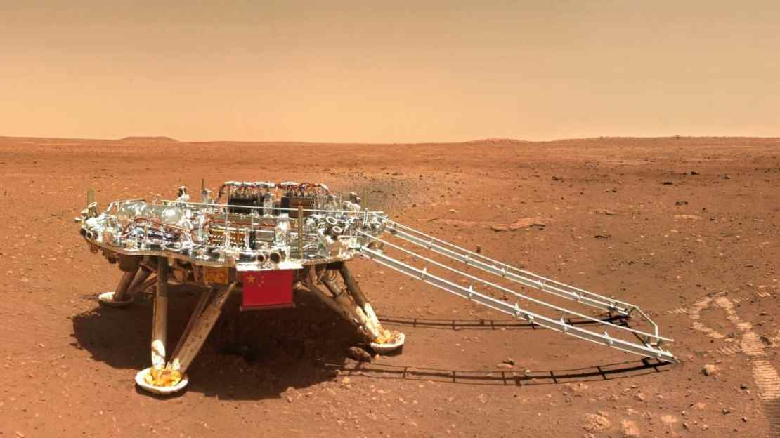 FOR USE WITH STORY CHINA MARS PHOTOS In this image released by the China National Space Administration (CNSA) on Friday, June 11, 2021, the landing platform with a Chinese national flag and outlines of the mascots for the 2022 Beijing Winter Olympics and Paralympics on Mars is seen from the rover Zhurong. China on Friday released a series of photos taken by its Zhurong rover on the surface of Mars, including one of the rover itself taken by a remote camera. (CNSA via AP)