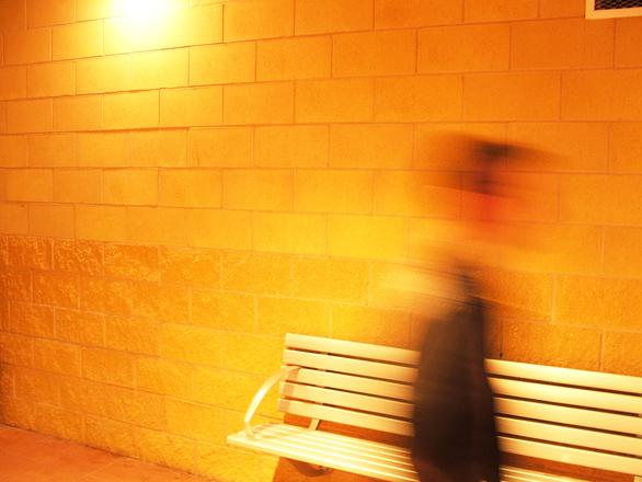 Persona caminando más allá de un banco