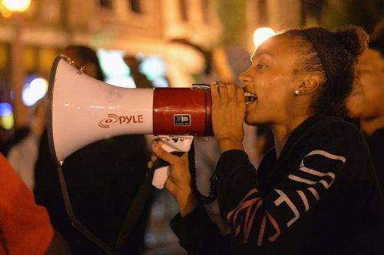 A Black woman protests in St. Louis following the police shooting of Michael Brown
