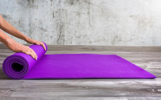 Woman rolling up yoga mat