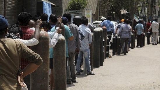 Family members of Covid-19 patients outside an oxygen-filling centre to refill their empty cylinders in New Delhi.(PTI)
