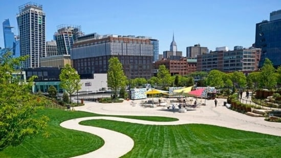 The Empire State Building can be seen from a distance from a winding path that leads to a casual outdoor dining area, Tuesday, May 18, 2021, at Little Island, in New York. Located atop Hudson River piers damaged during Superstorm Sandy, the park features two amphitheaters, a playground, winding paths and staircases, and views of the city from multiple angles. (AP)