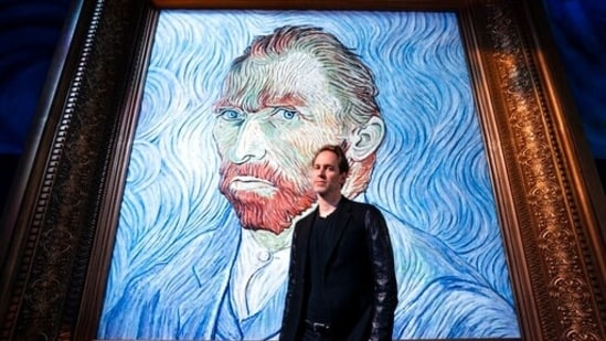 """David Korins stands beside a giant replica of celebrated painter Vincent Van Gogh's self portrait at a preview of the Immersive Van Gogh exhibit at Pier 36, Friday, June 4, 2021, in New York. Korins has added a ceiling installation that uses almost 8,000 paint brushes to thrillingly reproduce """"The Starry Night"""" and a station that uses artificial intelligence to give visitors an individualized letter from Van Gogh. (AP)"""
