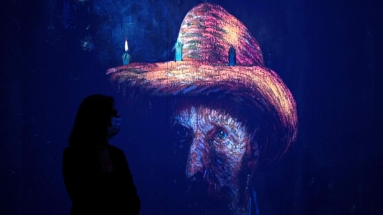 """People attend a media preview of the """"Immersive van Gogh"""" exhibit at Pier 36 on May 26, 2021 in New York City. - The art installation displays iconic works of post-Impressionist artist Vincent van Gogh, evoking his emotional and chaotic inner consciousness through art, light, music and movement.(AFP)"""