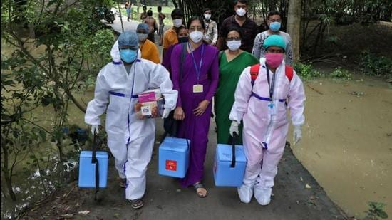 Healthcare workers carry Covishield doses to inoculate villagers during a door-to-door vaccination and testing drive at Uttar Batora Island in Howrah district in West Bengal state, India. (REUTERS)