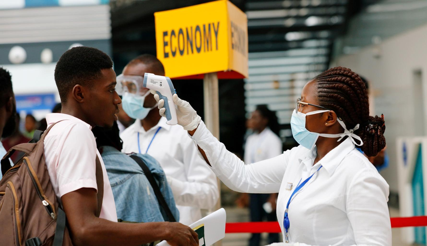 A health worker checks the temperature of a traveller as part of the coronavirus screening procedure at the Kotoka International Airport in Accra