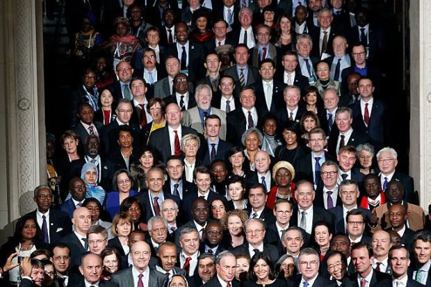 Thousands of male and female mayors from around the world pose vertically along a corridor at the Summit of Mayors at COP201 in Paris 2015