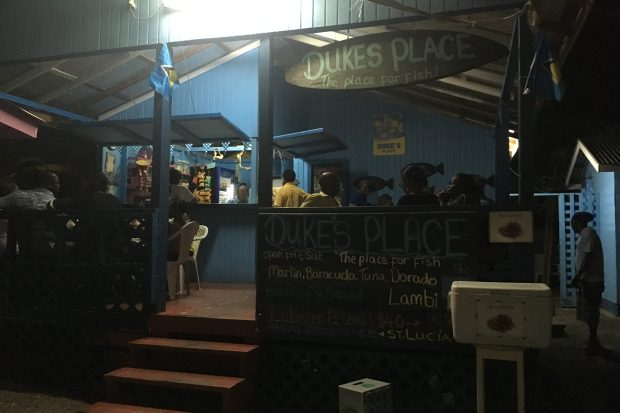 A dimly lit wooden shack has a sign saying 'Dukes Place', there is a blue wall in the shack and people sat inside