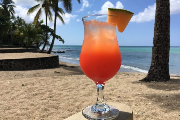 In the background is a white sandy beach and clear blue sea. In the foreground is a orange rum cocktail garnished with a slice of pineapple