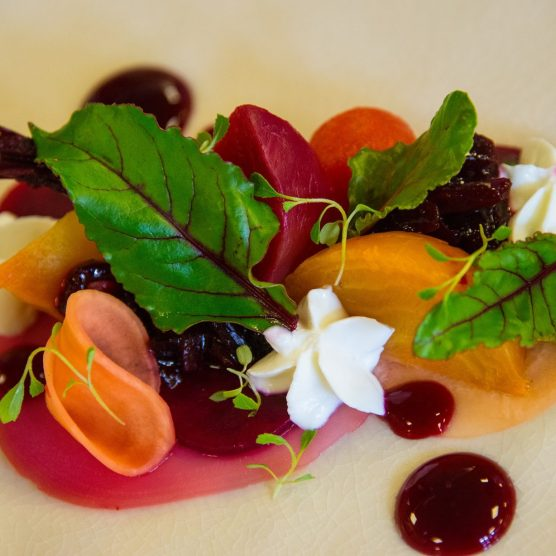 A plate is topped with chunks of colourful beetroot and mint leaves