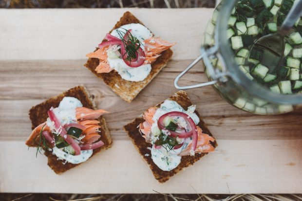 A pale wooden platter is topped with three pieces of toast. Each square is topped with dill creme fraiche, salmon and pickles