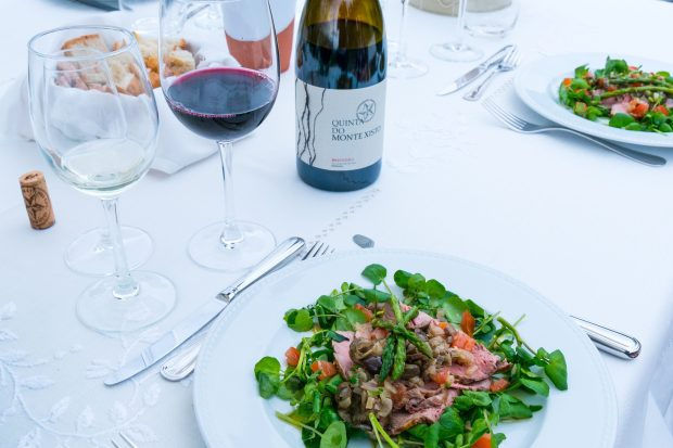 A table laid with a white table cloth is outside. On the table is a plate of food with green leaves, and a bottle of red wine. There is a glass of red and a glass of white wine in the photo