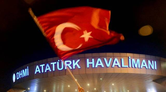 Turkey coup: A man waves a Turkish flag in front of Ataturk Airport during an attempted coup in Istanbul, Turkey July 16, 2016. REUTERS/IHLAS News Agency ATTENTION EDITORS - EDITORIAL USE ONLY. NO RESALES. NO ARCHIVES. TURKEY OUT. NO COMMERCIAL OR EDITORIAL SALES IN TURKEY.