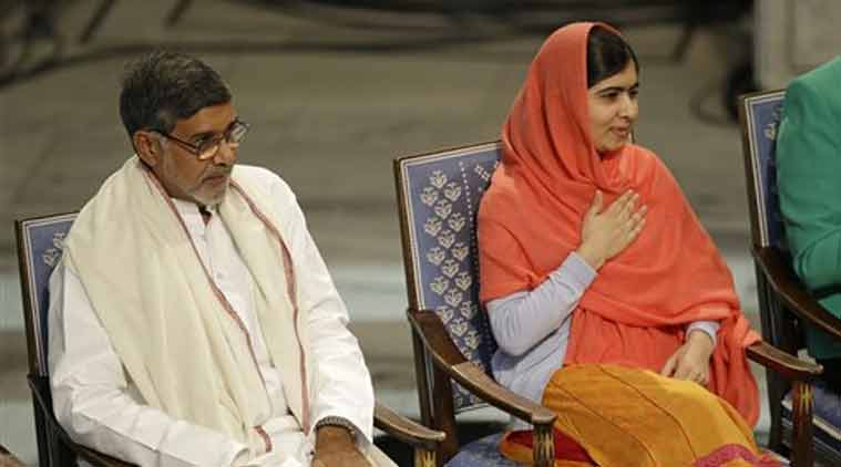 Nobel Peace Prize winners Malala Yousafzai from Pakistan, right, and Kailash Satyarthi of India take their seats during the Nobel Peace Prize award ceremony in Oslo (Source: AP)