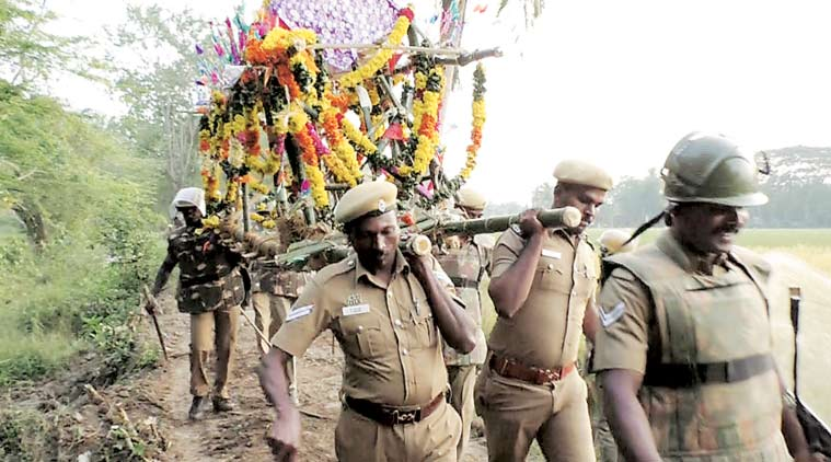 Policemen carry the body of Chellamuthu through the forest path for burial at Vazhavur, Nagapattinam.