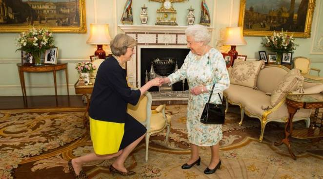 Queen Elizabeth II welcomes Theresa May, left, at the start of an audience in Buckingham Palace, London, where she invited the former Home Secretary to become Prime Minister and form a new government, Wednesday July 13, 2016. David Cameron had resigned the post in an earlier meeting with the queen. (Dominic Lipinski/Pool Photo via AP)
