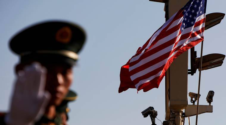 A paramilitary policeman gestures under a pole with security cameras, U.S. and China's flags.