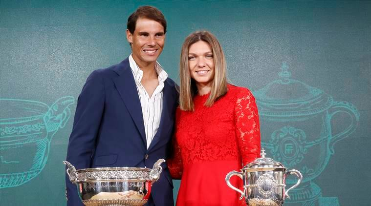 Defending champions Spain's Rafael Nadal, left, and Romania's Simona Halep pose next to the cups during the draw of the French Open tennis tournament at the Roland Garros stadium in Paris