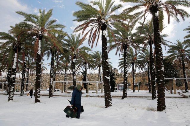 Un homme marche àJérusalem, oùl'épaisseur de neige atteignait... (PHOTO DARREN WHITESIDE, REUTERS)