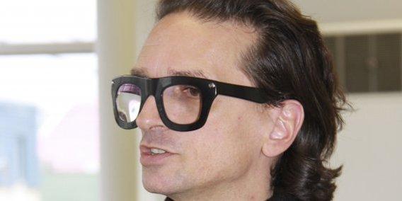 Derrières ses lunettes aux énormes montures noires qui... (Claudine Girard, Le Quotidien)