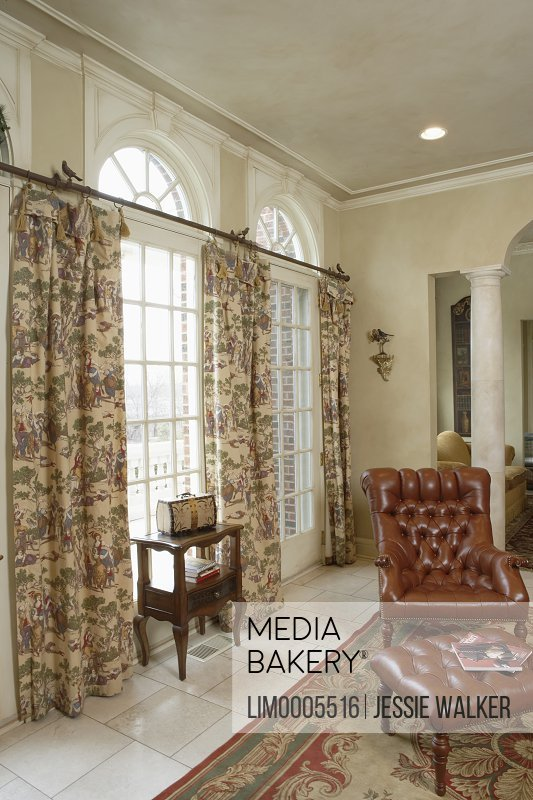 https www mediabakery com lim0005516 window treatments palladian windows above pastoral printed curtains small birds are sitting on the curtain rod leather chair and ottoman marble tile floor with area rug html