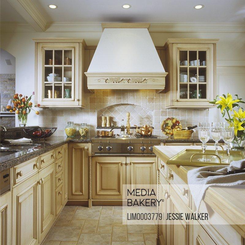https www mediabakery com lim0003779 kitchen creamy blonde wood cabinets with granite countertop stone tile floor island with wood countertop hood with wood trim copper pot on stove tile backsplash molding html