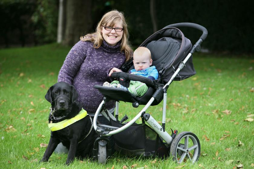 A woman poses with her baby in a stroller and her guide dog