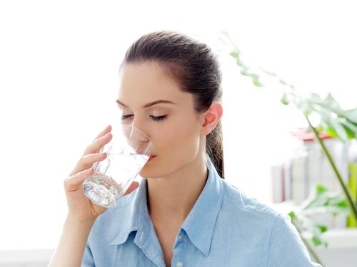 Woman drinking glass of water in the morning
