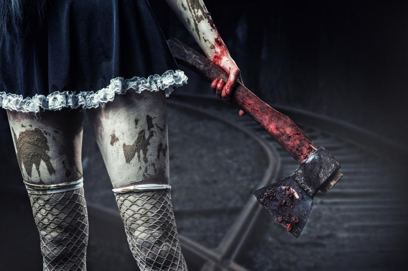 Dirty woman's hand holding a bloody axe outdoor in night forest