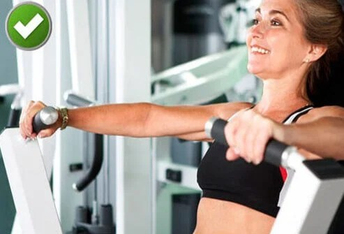 Woman using chest press machine at gym