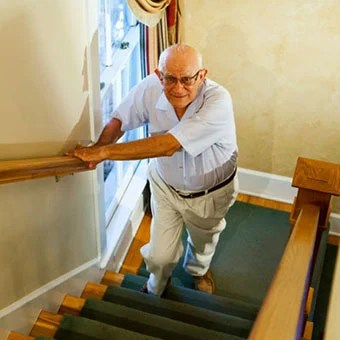 A man experiences hip pain while walking up the stairs.