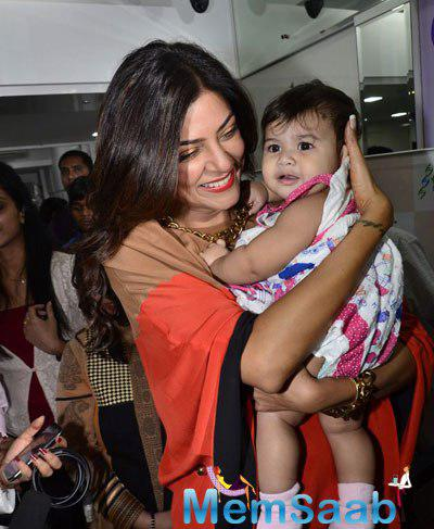 Sushmita Sen Cool Smiling Pose With A Kid During The Launch Of A Genetic Based Anti-Ageing Solution