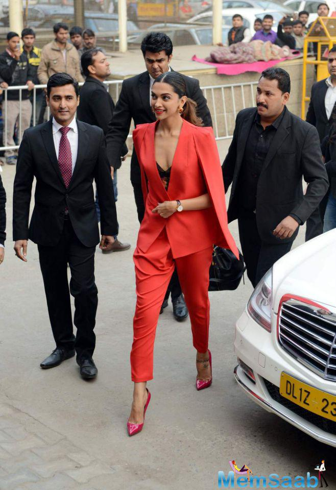 Deepika wearing a red pantsuit featuring overcoat, The actress finished out her look with a middle parted ponytail and earrings