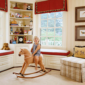 Boy on rocking horse in dog themed room