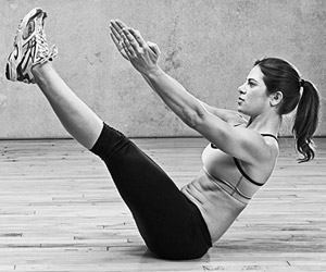 a woman doing boat pose