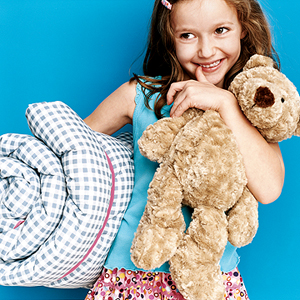 girl holding her bear and sleeping bag