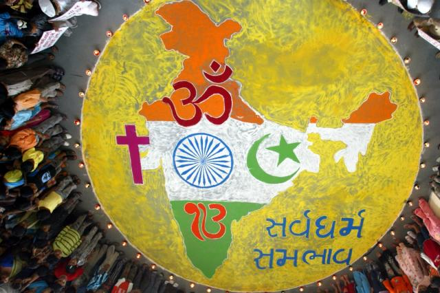 School children stand around a drawing of a map of India together with the symbols of Islam, Hinduism, Christianity and Sikhism to spread the message of peace and harmony in Ahmedabad. The message written in Hindi reads: