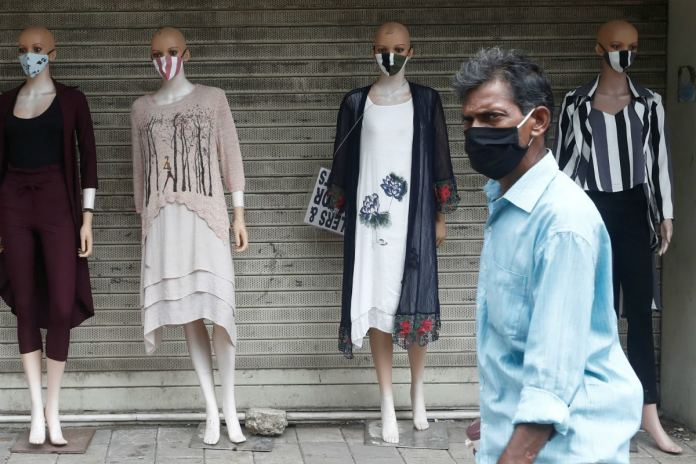 A man wearing a mask walks past mannequins in Mumbai. (Reuters)